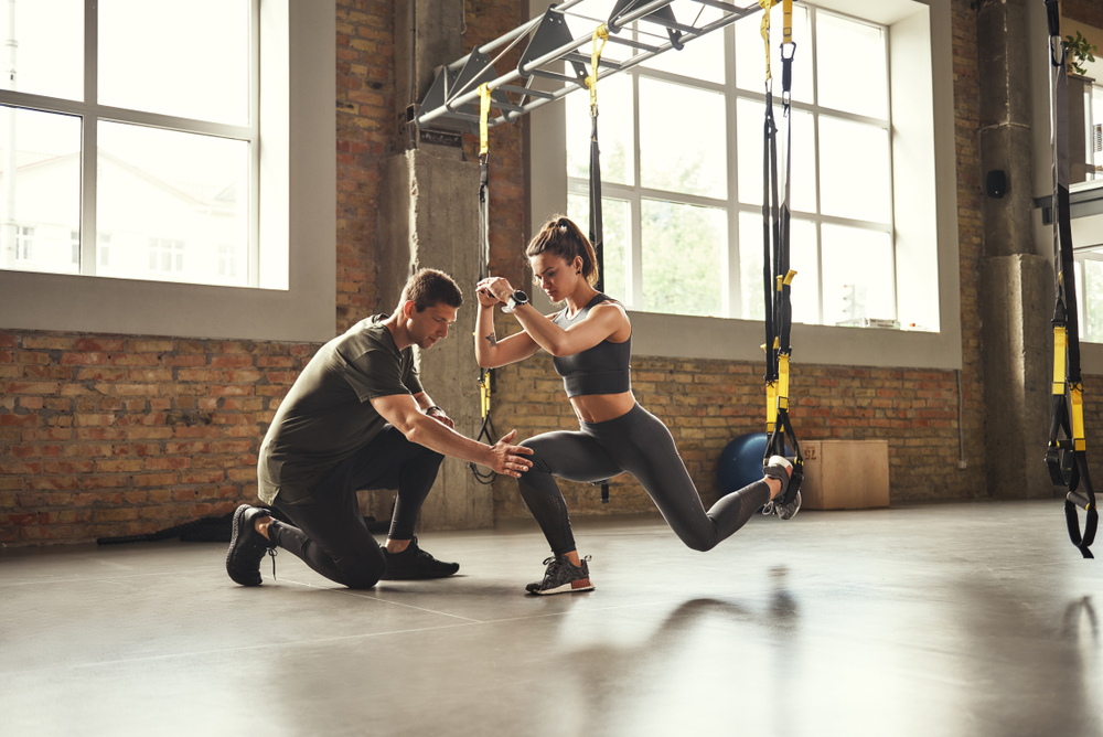 woman and man in the gym exercising